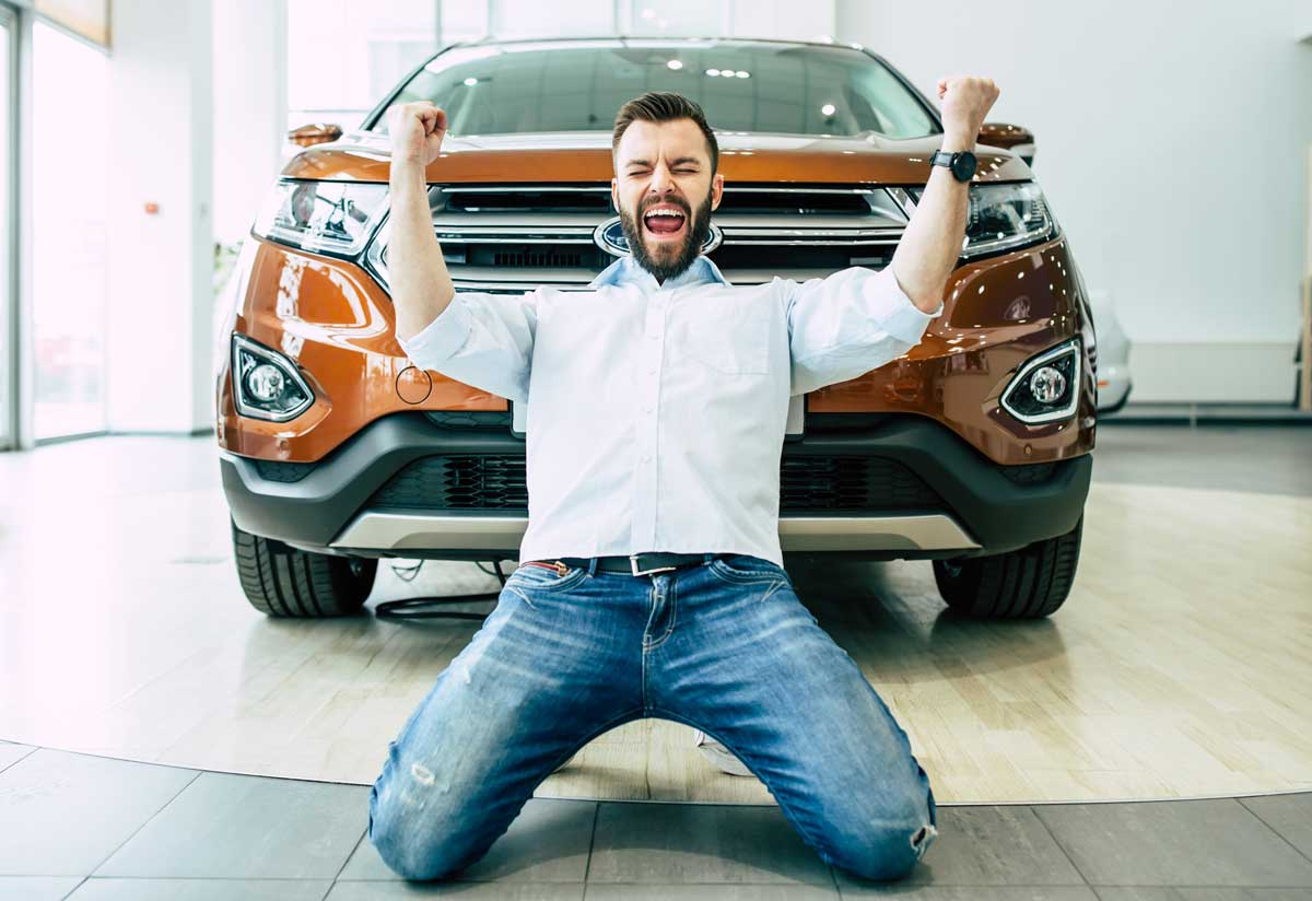 Happy man in front of a new car